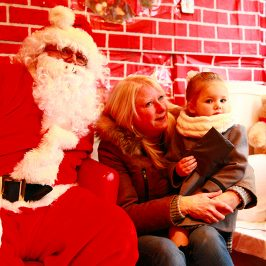 Traditional Father Christmas in Santa's Grotto with mother and child at Roman Road Winter Festival 2014