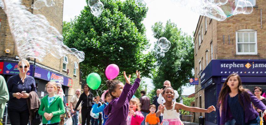 Children chasing giant bubbles at Roman Road Festival 2014