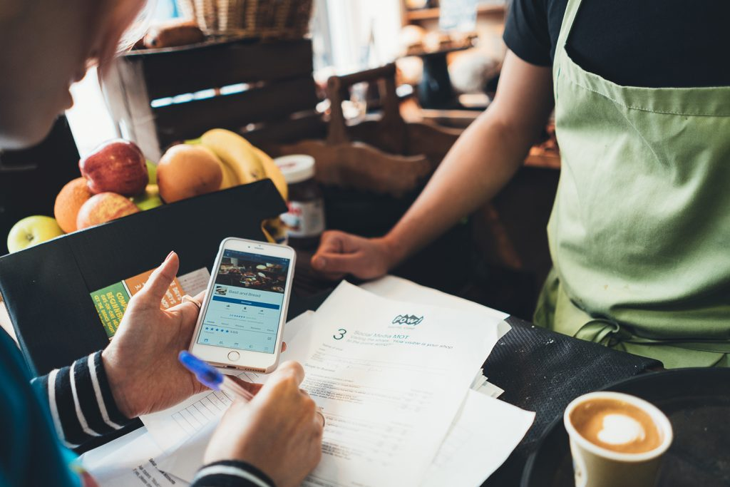 Woman holding iPhone filling in forms in coffee shop